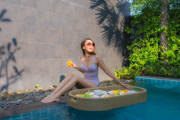 Glückliches lächeln der jungen asiatischen frau des porträts genießen mit schwimmendem frühstückstablett im schwimmbad im hotel