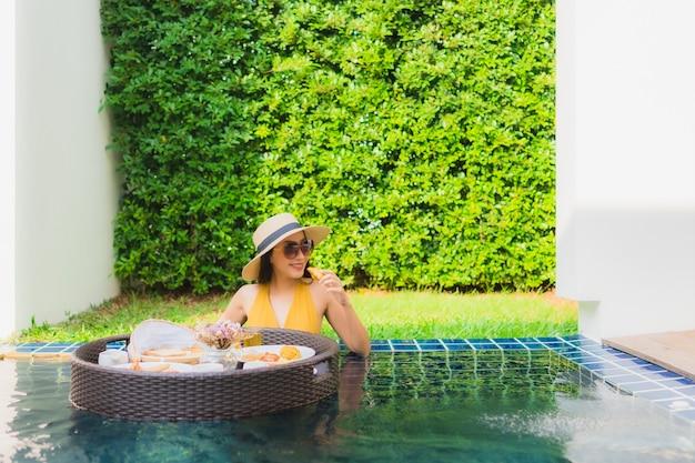 Glückliches lächeln der schönen jungen asiatischen frau des porträts entspannen mit frühstück, das um schwimmbad schwimmt