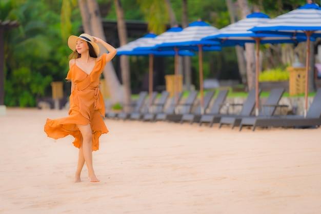 Glückliches lächeln der schönen jungen asiatischen frau des porträts entspannen sich auf dem strandseeozean