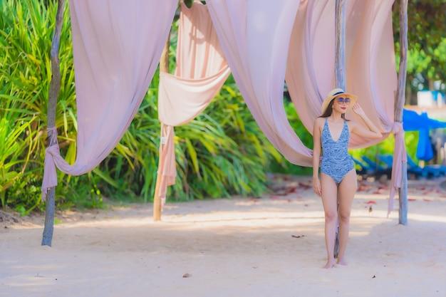 Glückliches lächeln der schönen jungen asiatischen frau des porträts entspannen sich auf dem tropischen strandseeozean für freizeitreise