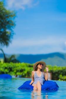 Glückliches lächeln der schönen jungen asiatischen frau des porträts entspannen sich im swimmingpool am neary seeozeanstrand des hotelerholungsortes auf blauem himmel
