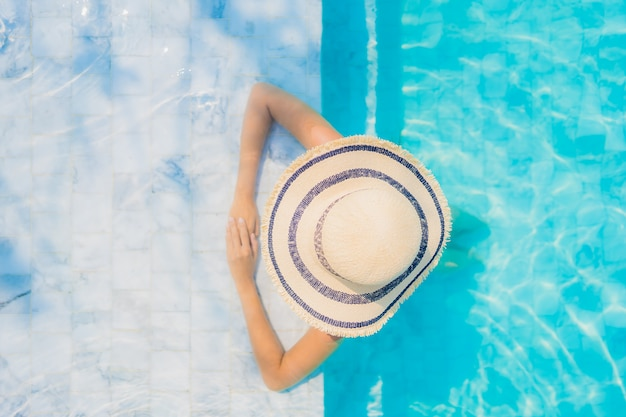 Glückliches lächeln der schönen jungen asiatischen frau des porträts entspannen sich im swimmingpool für reiseferien