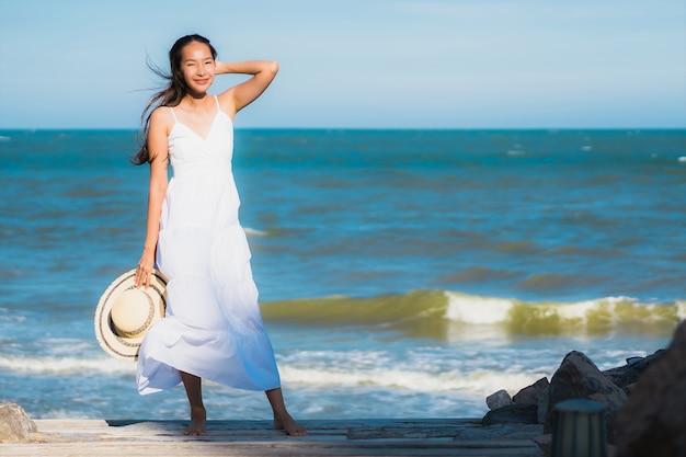 Glückliches lächeln der schönen jungen asiatischen frau des porträts entspannen sich um neary strand und meer