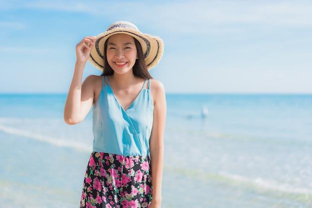 Glückliches lächeln der schönen jungen asiatischen frau des porträts entspannen sich um strandozean und -meer