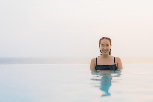 Glückliches lächeln der schönen jungen asiatischen frau des porträts entspannen sich um swimmingpool im hotelerholungsort