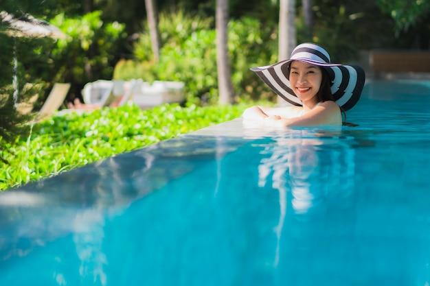 Glückliches lächeln der schönen jungen asiatischen frau des porträts im swimmingpool um erholungsort und hotel