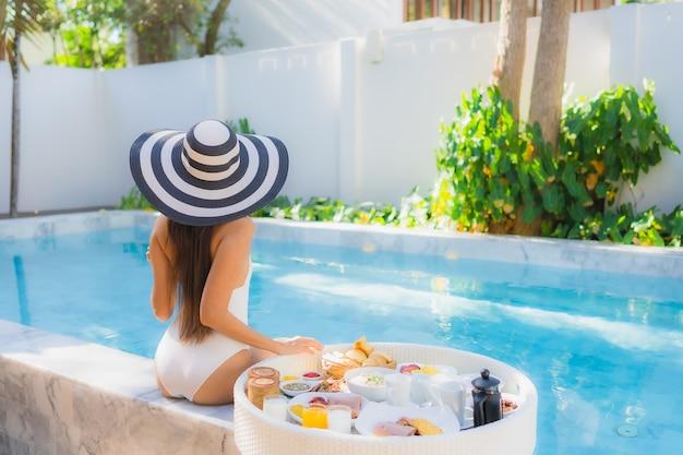 Glückliches lächeln der schönen jungen asiatischen frau des porträts mit schwimmendem frühstück im tablett am schwimmbad