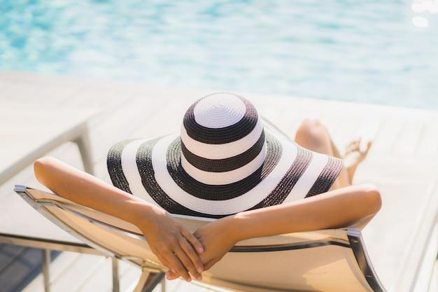 Glückliches lächeln der schönen jungen asiatischen frau des porträts und entspannen sich um swimmingpool im hotelerholungsort
