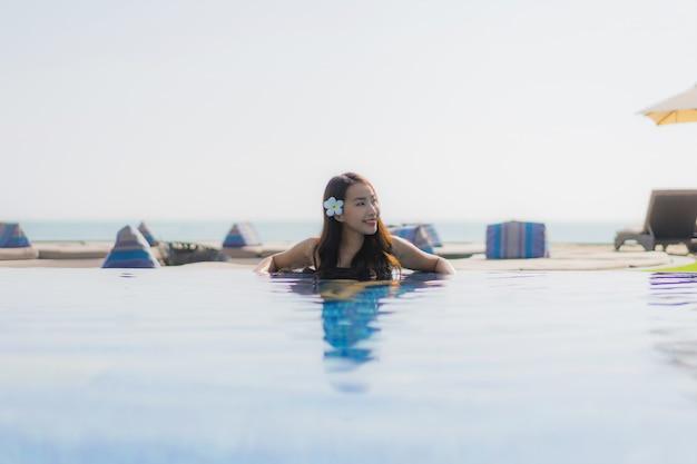 Glückliches lächeln der schönen jungen asiatischen frau und entspannen sich im swimmingpool