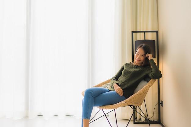 Glückliches lächeln der schönen jungen asiatischen frauen des porträts entspannen sich das sitzen auf sofastuhl
