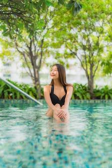 Glückliches lächeln der schönen jungen asiatischen frauen des porträts entspannen sich swimmingpool im freien im erholungsort