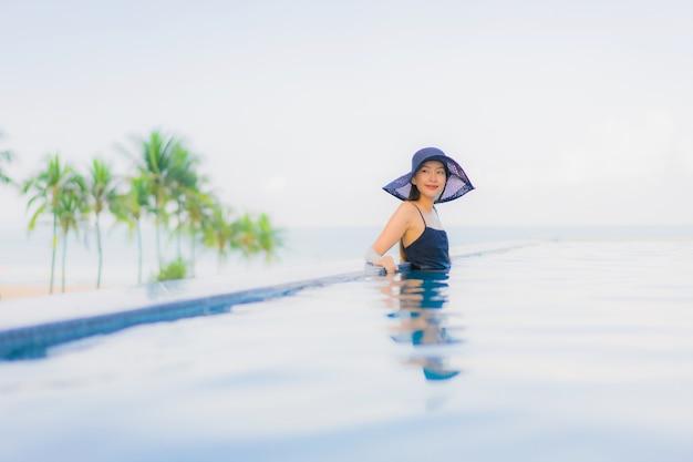 Glückliches lächeln der schönen jungen asiatischen frauen des porträts entspannen sich swimmingpool im freien im hotel