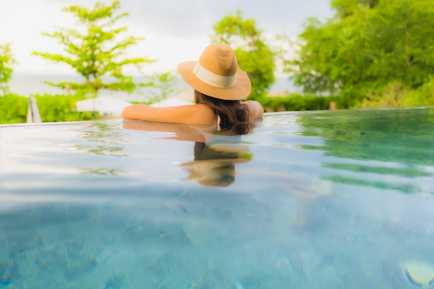 Glückliches lächeln der schönen jungen asiatischen frauen des porträts entspannen sich um swimmingpool im freien im hotel