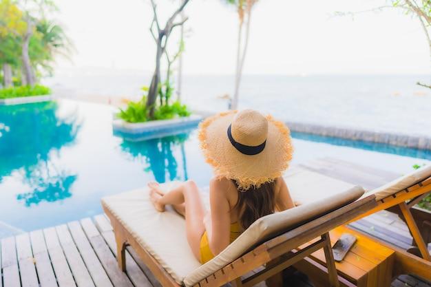 Glückliches lächeln der schönen jungen asiatischen frauen des porträts entspannen sich um swimmingpool im freien