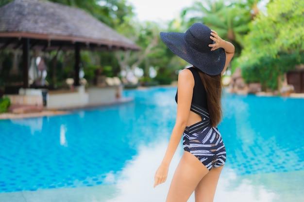 Glückliches lächeln der schönen jungen asiatischen frauen des porträts entspannen sich um swimmingpool