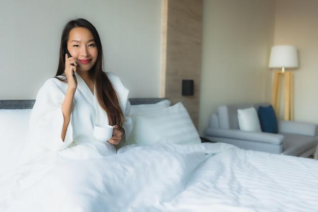 Glückliches lächeln der schönen jungen asiatischen frauen des porträts mit kaffee und handy