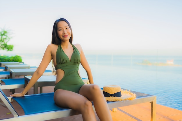 Glückliches lächeln der schönen jungen asiatischen frauen entspannen sich um swimmingpool im freien im hotelerholungsort für reise in den feiertagsferien