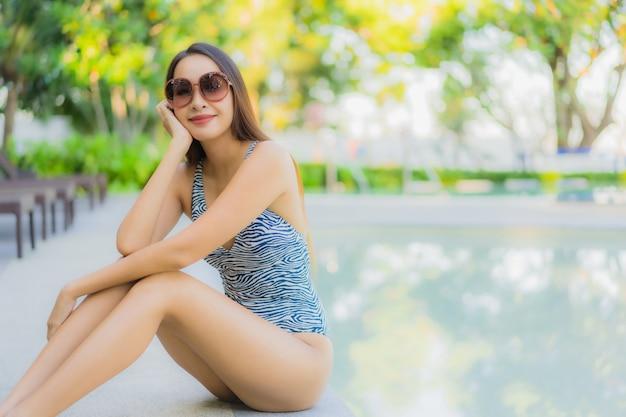 Glückliches lächeln der schönen jungen asiatischen frauen entspannen sich um swimmingpool im freien im hotelerholungsort