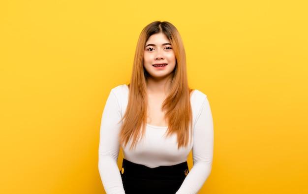 Glückliches lächeln, liebe und entspannung asiatische frau, die glücklich auf gelbem hintergrund lächelt