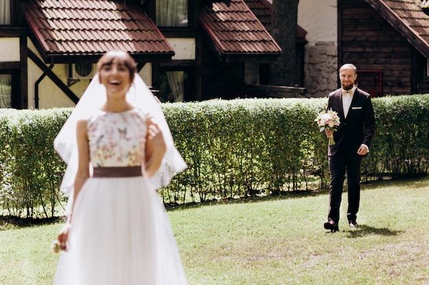 Glückliches lächelnbraut, das den bräutigam mit blumenstrauß wartet