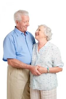 Glückliches lächelndes älteres paar, das zusammen mit einer umarmung lokalisiert auf weiß steht