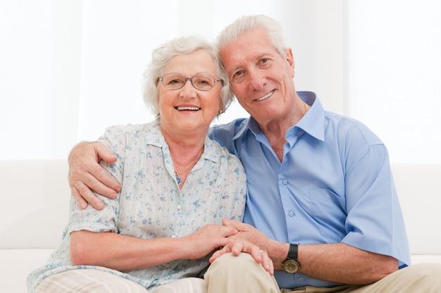 Glückliches lächelndes älteres paar, das zusammen zu hause umarmt