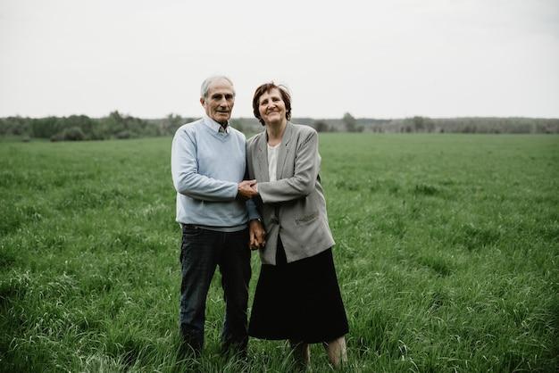 Glückliches lächelndes älteres paar verliebt in natur, spaß haben. älteres paar auf der grünen wiese. nettes älteres paar, das im frühlingswald geht und umarmt
