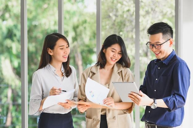 Glückliches lächelndes asiatisches geschäftsteam, das zusammen im büro diskutiert und brainstorming durchführt