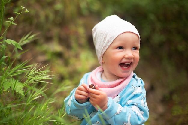 Glückliches lächelndes baby, das hellblaue jacke und weißen hut trägt, die draußen stehen.