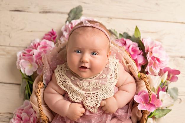 Glückliches lächelndes baby in einem rosa kleid liegt auf ihrem rücken in einem blumenkorb