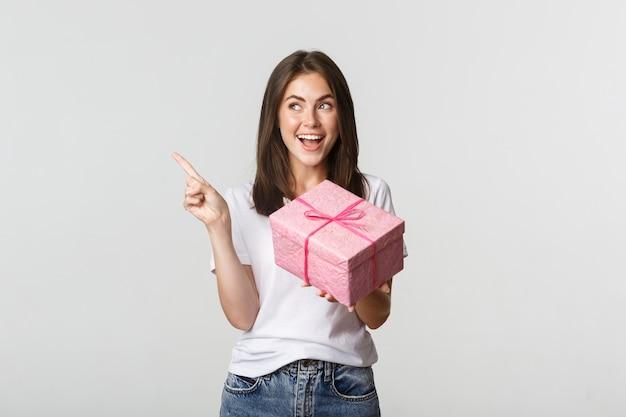 Glückliches lächelndes brünettes mädchen, das geburtstagsgeschenk hält und finger links am logo zeigt.