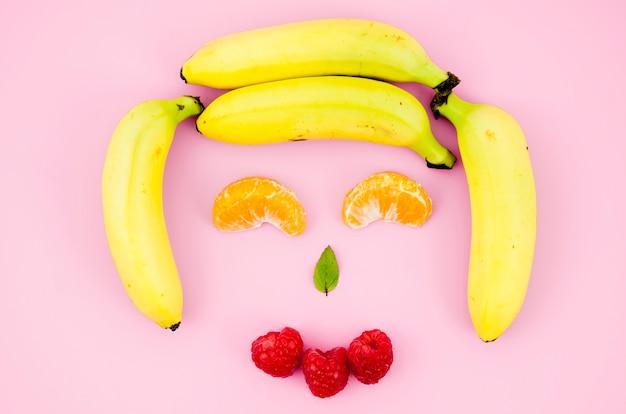 Glückliches lächelndes fruchtgesicht auf heller oberfläche