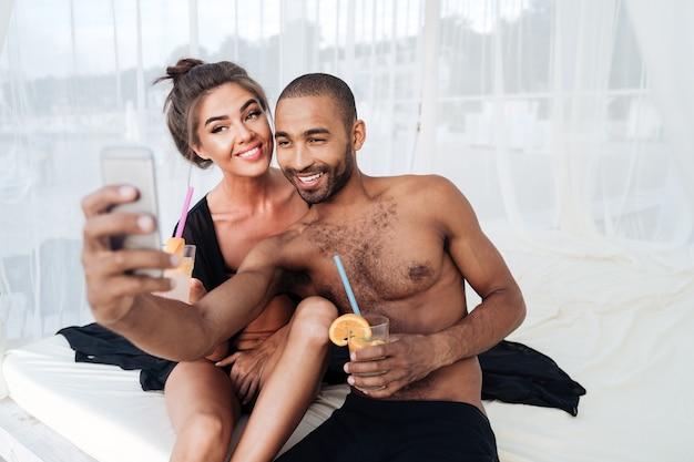 Glückliches lächelndes gemischtrassiges paar, das selfie macht und cocktails am strand hält Premium Fotos