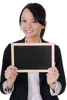 Glückliches lächelndes geschäftsmädchen, das leere tafel, nahaufnahmeporträt auf weißem hintergrund hält