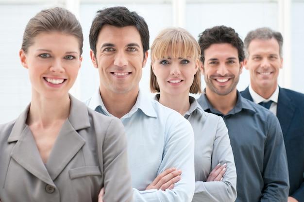 Glückliches lächelndes geschäftsteam, das in einer reihe im büro steht
