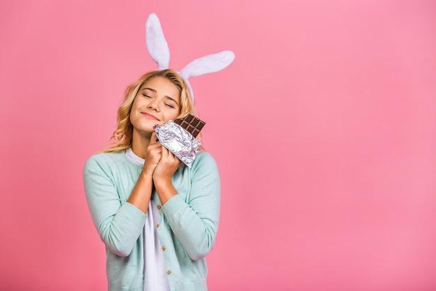 Glückliches lächelndes jugendlich oder kindermädchen, das leckere schokolade mit leerem kopienraum beißt