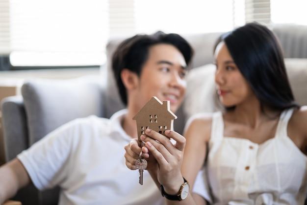 Glückliches lächelndes junges asiatisches paar, das ein musterhaus hält und zusammen tanzt