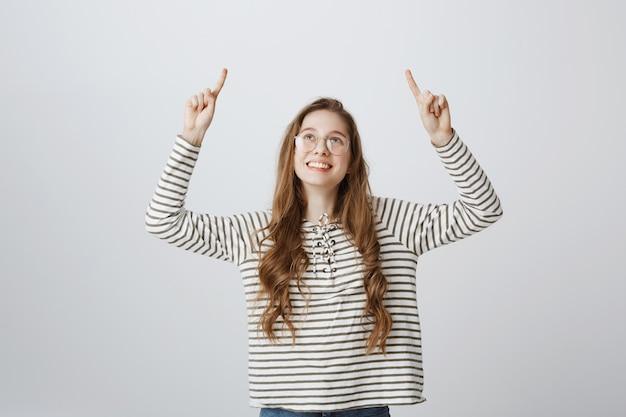 Glückliches lächelndes junges mädchen, das finger nach oben schaut und zeigt
