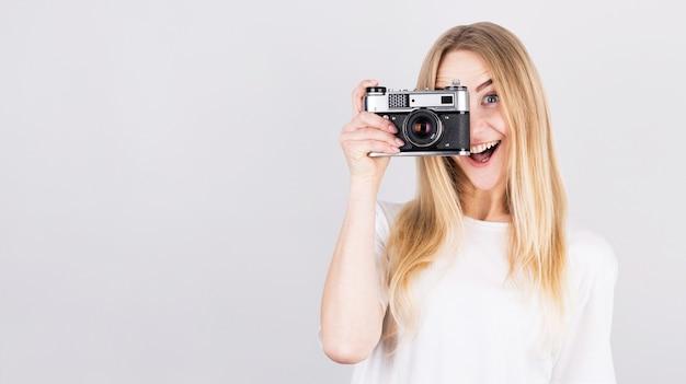 Glückliches lächelndes junges mädchen, das kamera hält und fotos macht