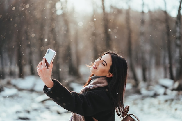 Glückliches lächelndes junges mädchen oder junge frau, die selfie durch smartphone im winterpark nimmt