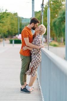 Glückliches lächelndes junges paar, das auf brücke umarmt und küsst