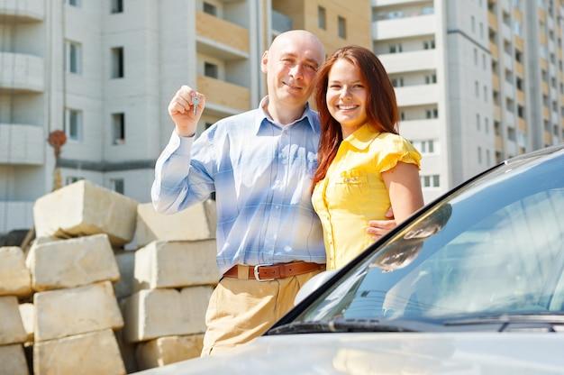 Glückliches lächelndes junges paar, das ein schlüsselpaar ihres neuen hauses zeigt