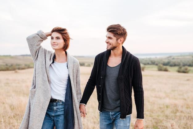 Glückliches lächelndes junges paar, das einen spaziergang durch die wiese genießt
