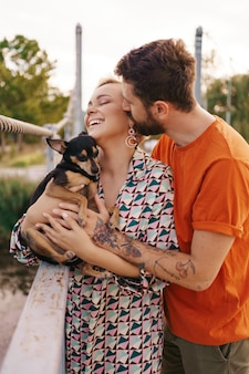 Glückliches lächelndes junges paar, das ihren hund auf brücke umarmt
