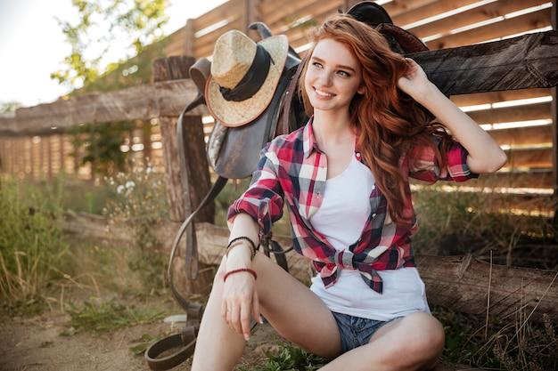 Glückliches lächelndes junges rothaariges cowgirl, das am ranchzaun ruht