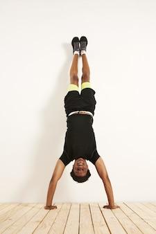 Glückliches lächelndes junges schwarzes modell in schwarzer und gelber trainingskleidung, die handstand gegen eine weiße wand auf holzboden tut.