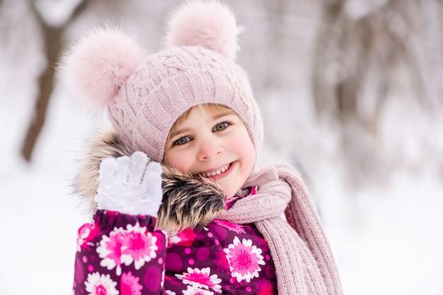 Glückliches lächelndes kind am schneehintergrund während des gehens