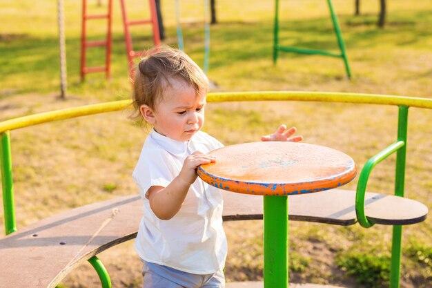 Glückliches lächelndes kind, das auf einem spielplatz spielt