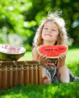 Glückliches lächelndes kind, das draußen im frühlingspark wassermelone isst