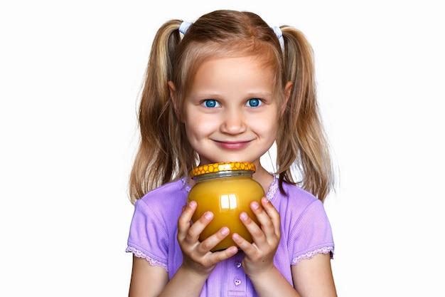 Glückliches lächelndes kind, das ein glas honig in den händen auf hellem hintergrund hält